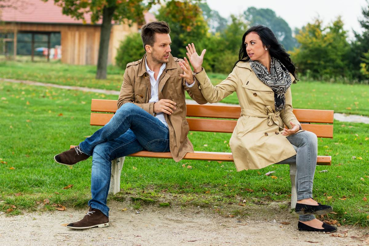 couple on bench in park upset