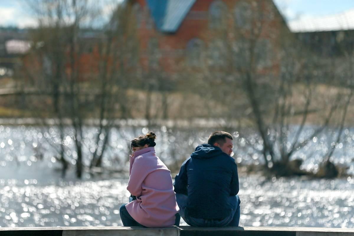 couple sitting at water's edge ivanovo region russia