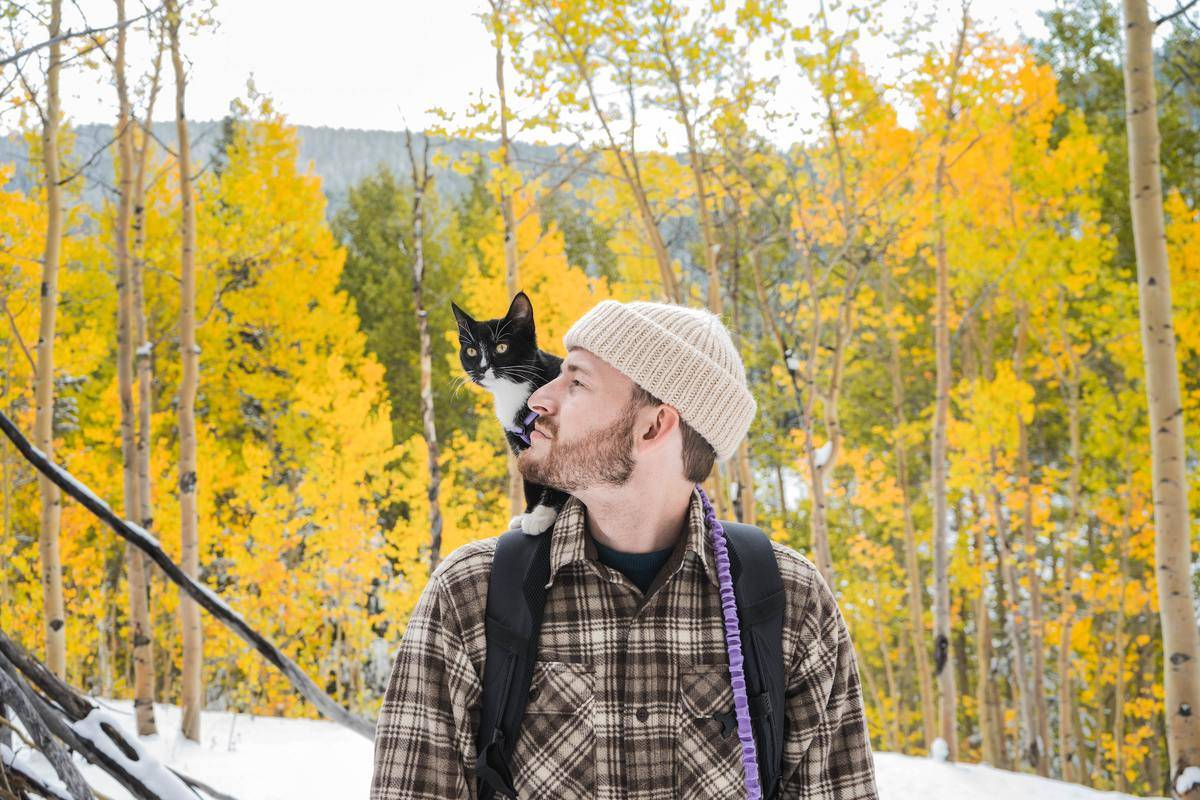 man with cat on shoulder outdoors in the winter