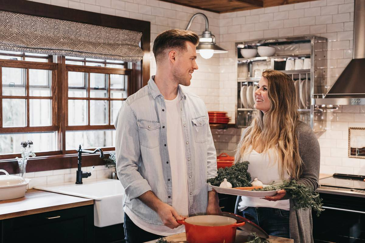 man and woman cook together in the kitchen