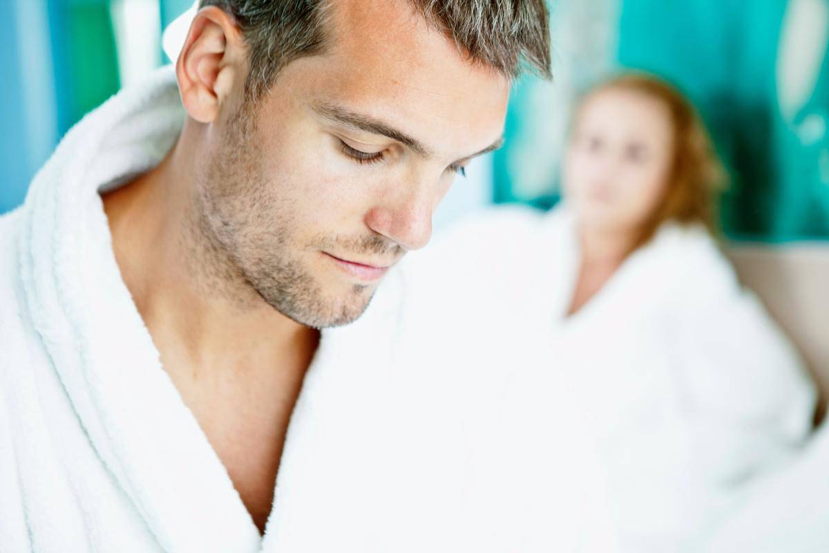 couple looks angry in robes in bed