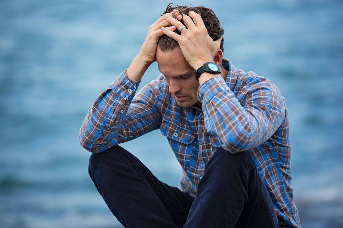 man in blue plaid shirt holds his hair in stress