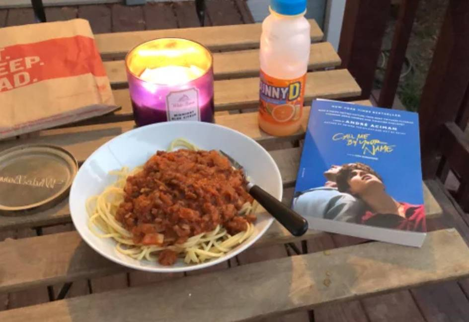 bowl of spaghitti with sauce, lit candle, bottle of sunny d, and book on a table