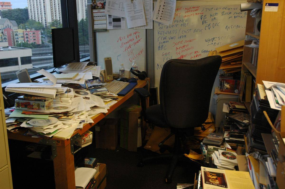 desk and area covered in papers and clutter