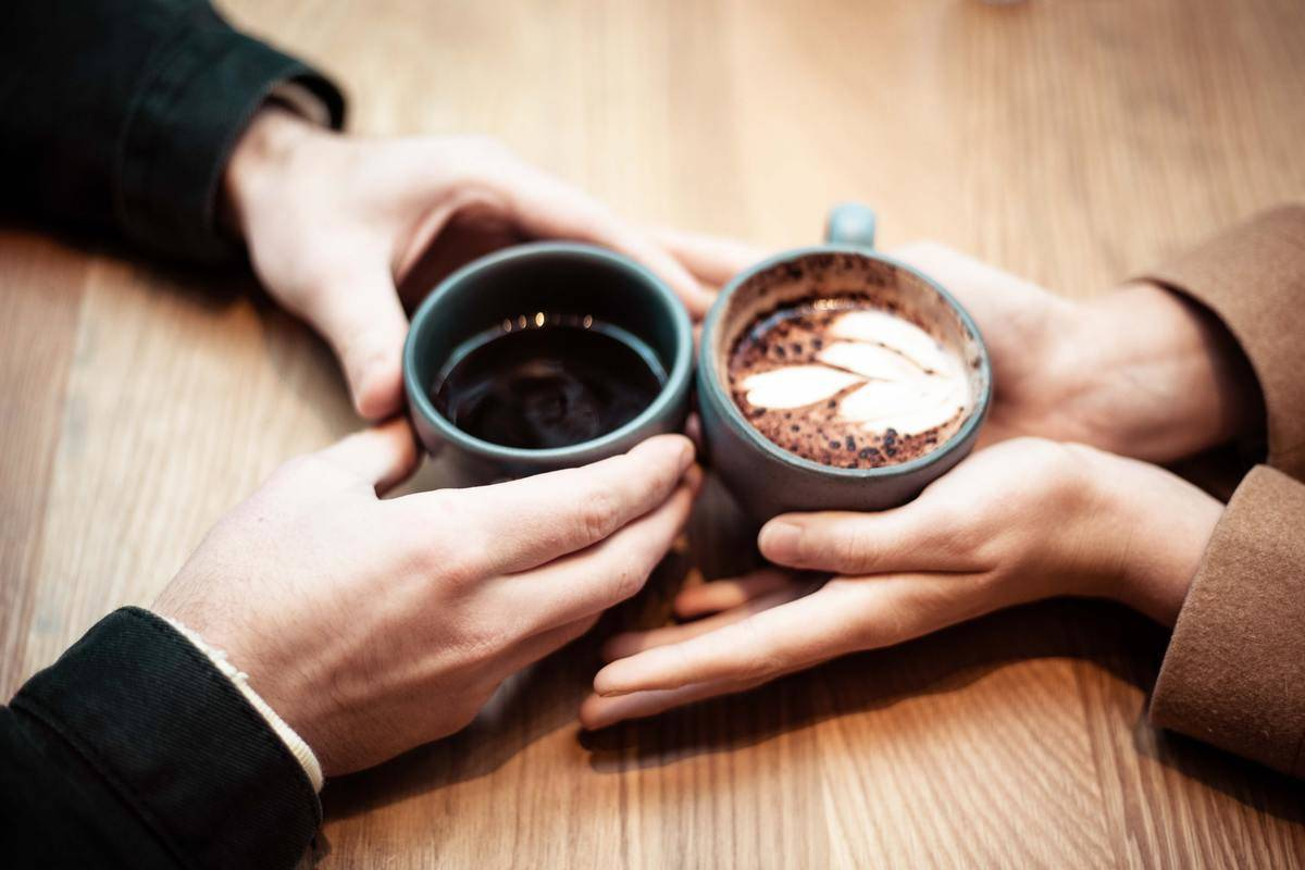 people with coffe mugs touching with hands