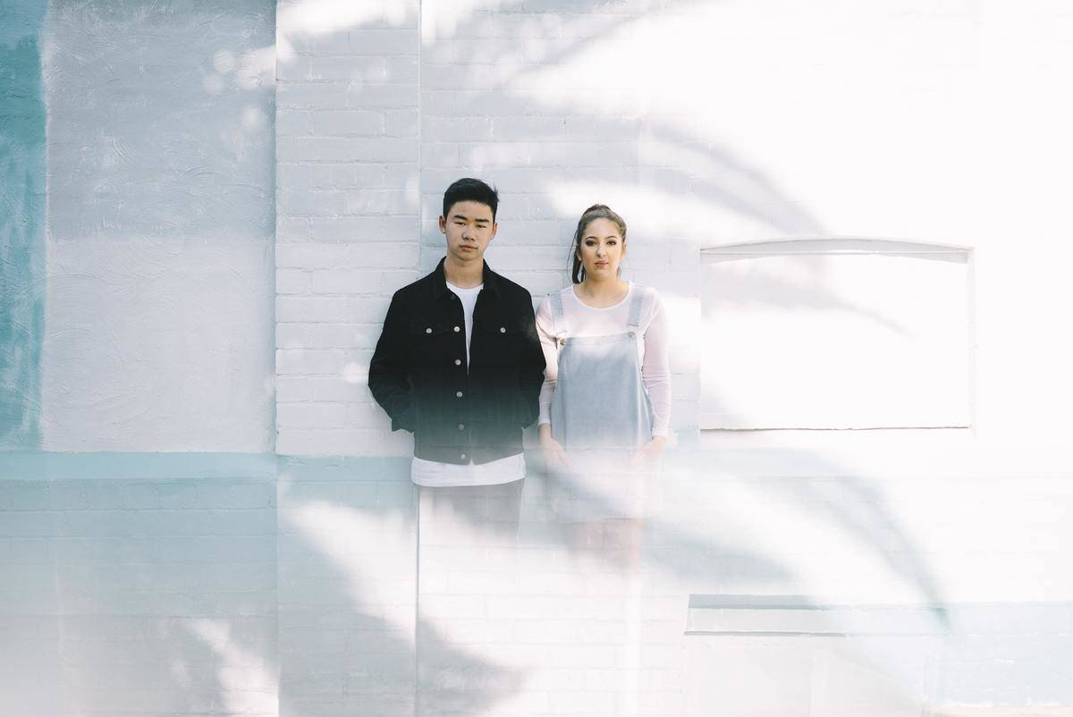 young couple standing against white wall, fading out below the torso