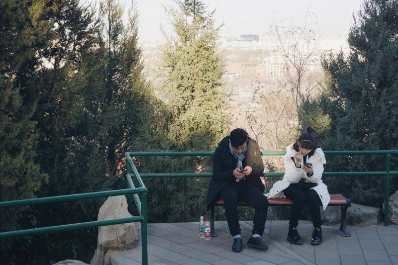 two people on phones outside not looking