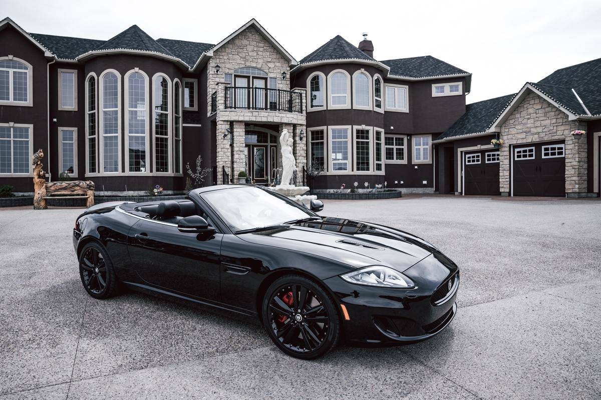 fancy car is parked in front of big home