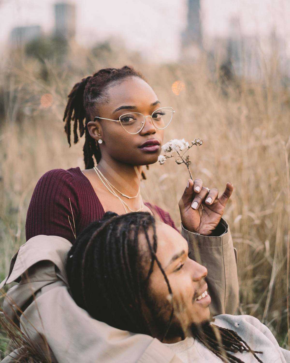 a couple sitting in a field smelling flowers