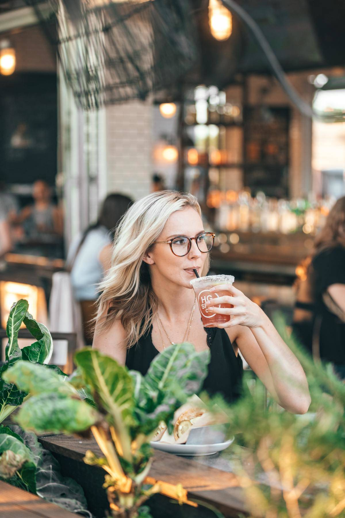 woman drinking iced coffee, staring at something off-camera
