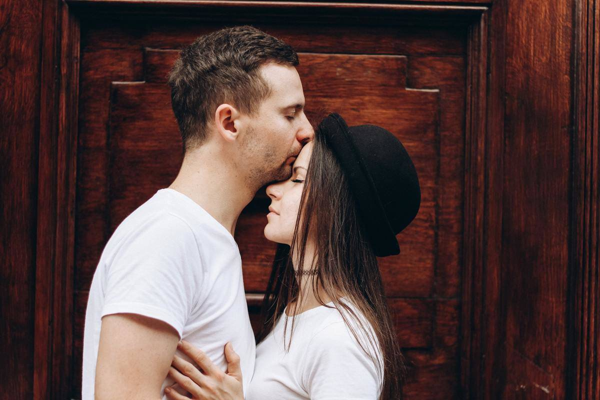guy kissing girl on the forehead