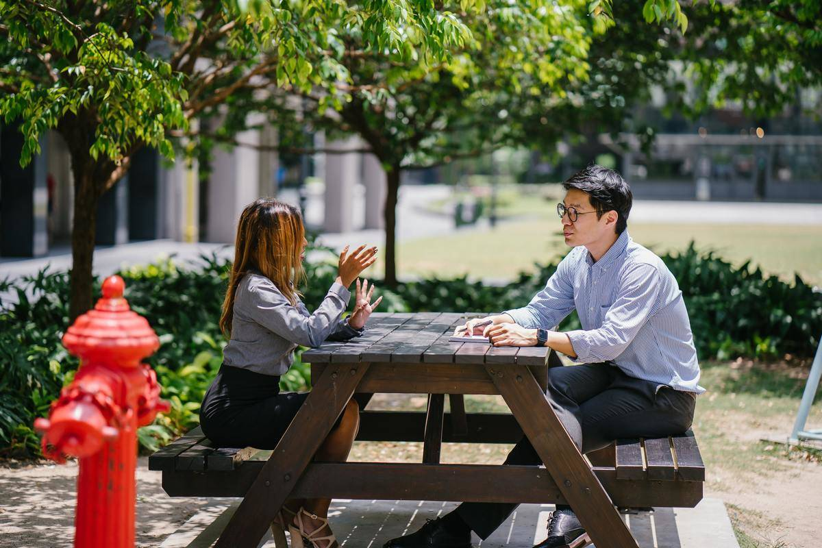 two people talking picnic table outside sunny