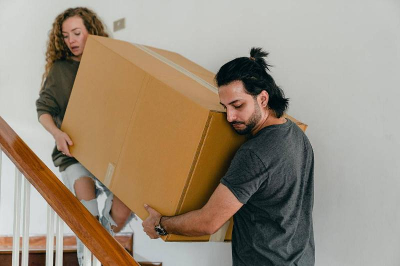 man and woman carrying box down stairs