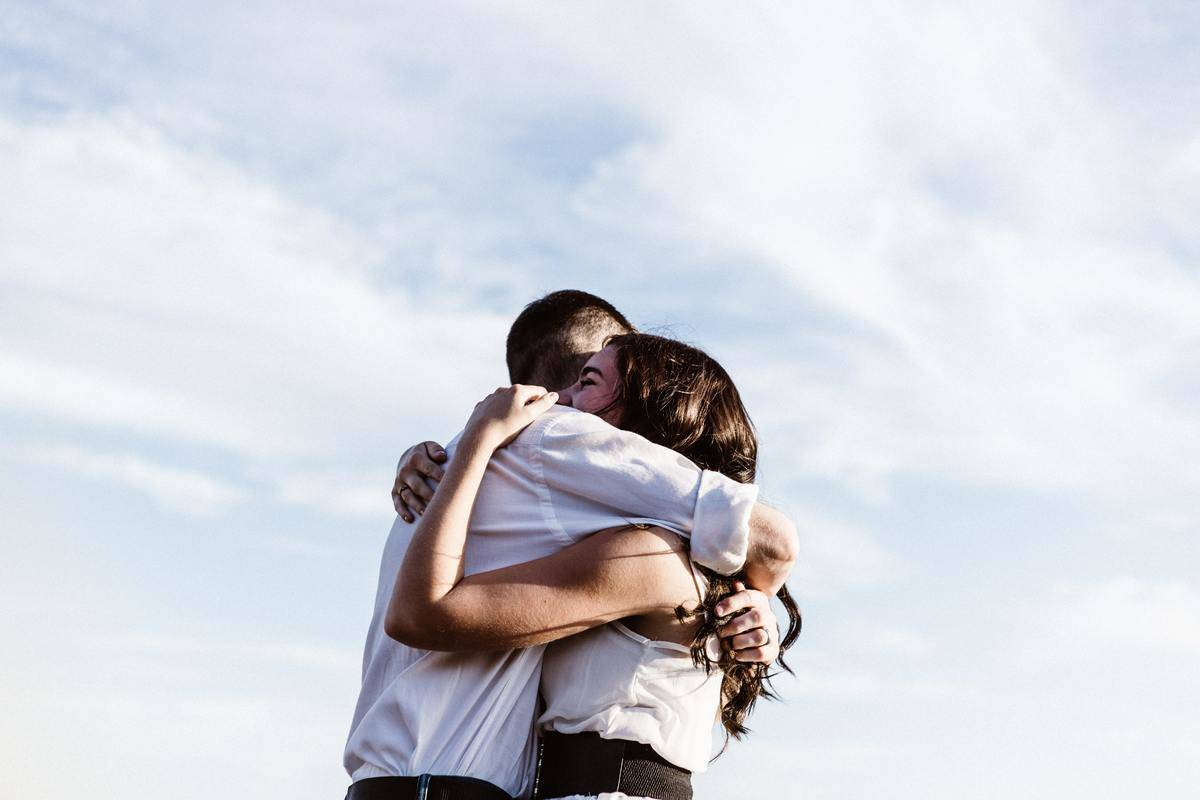 man and woman hug by the blue sky