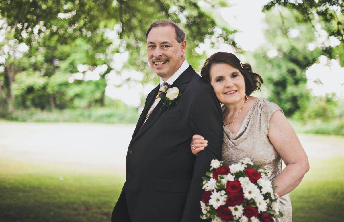 older man and woman in fancy clothes with flowers