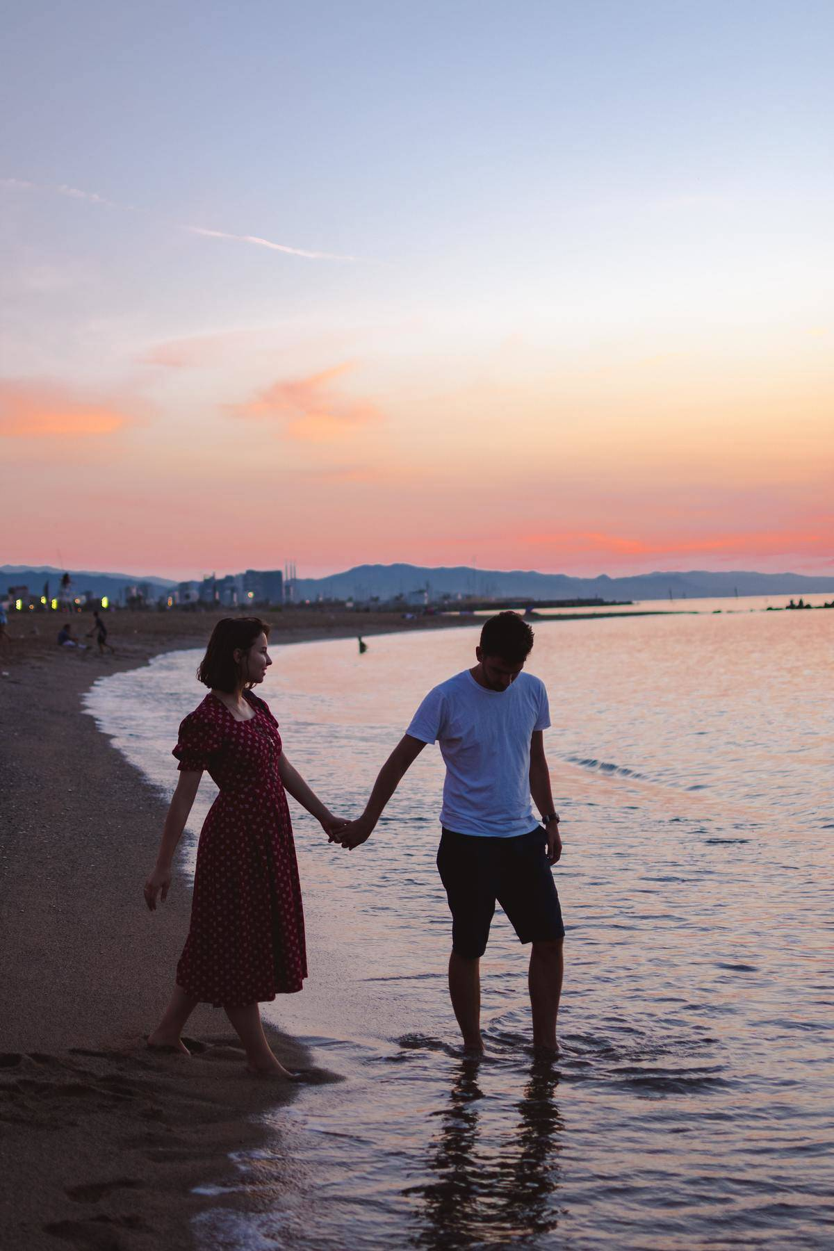 man and woman walking shoreline holding hands