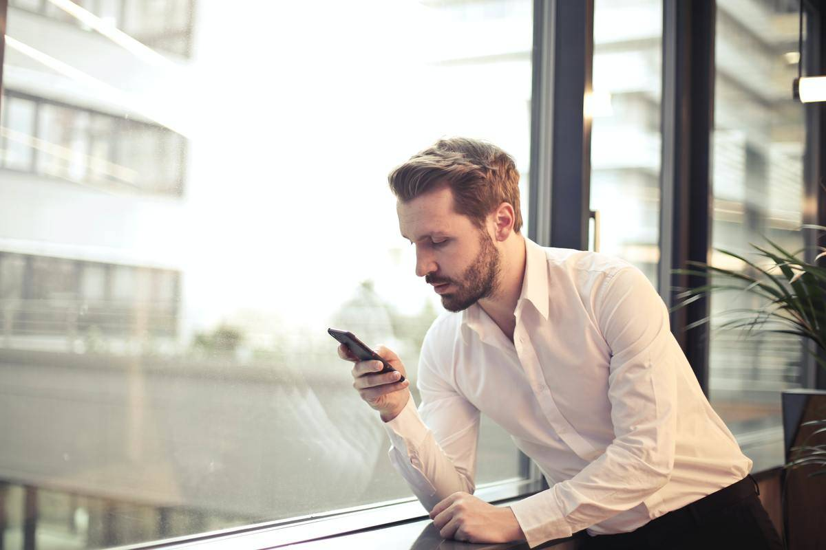 man leaning by window looking at phone screen