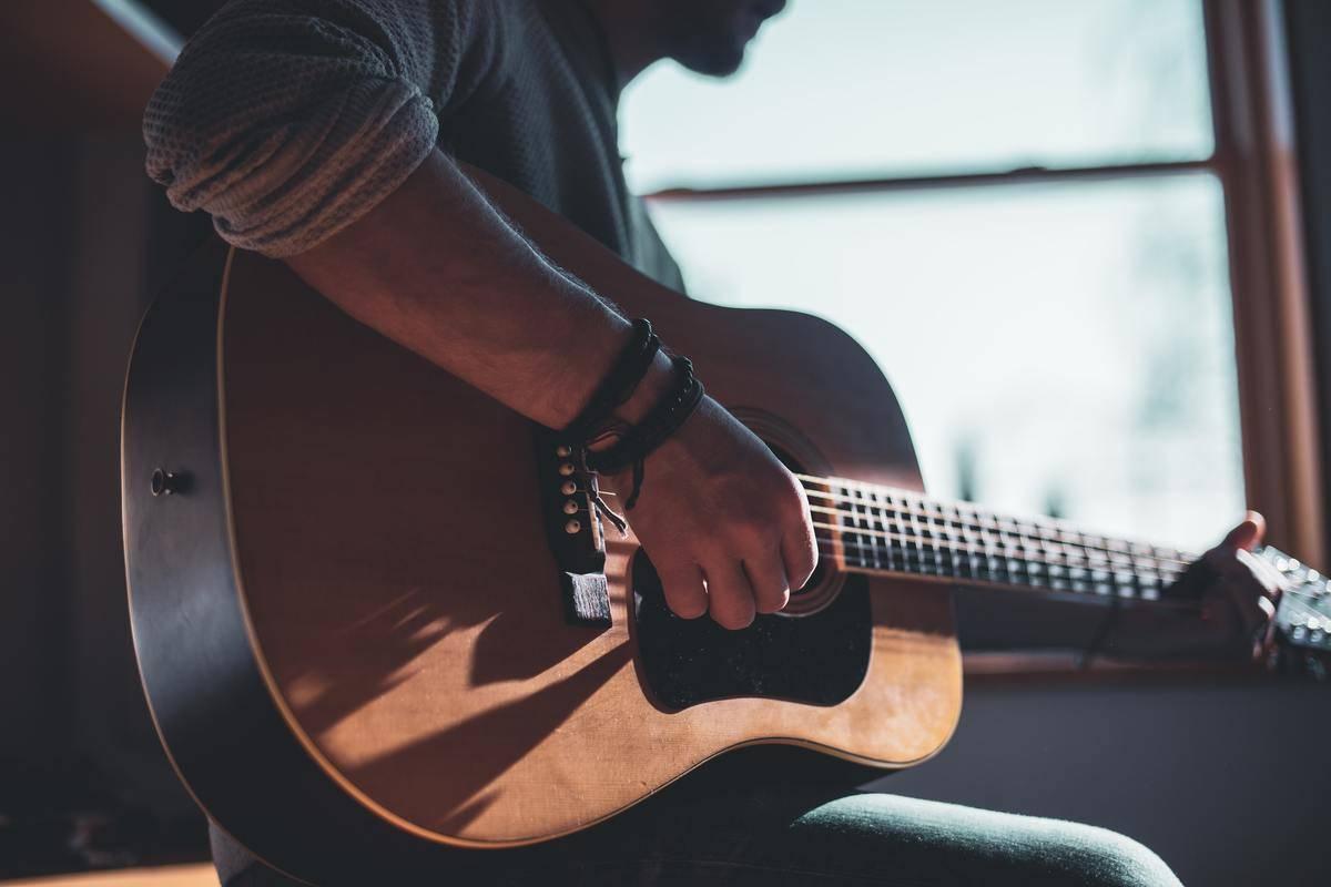 man strumming on guitar