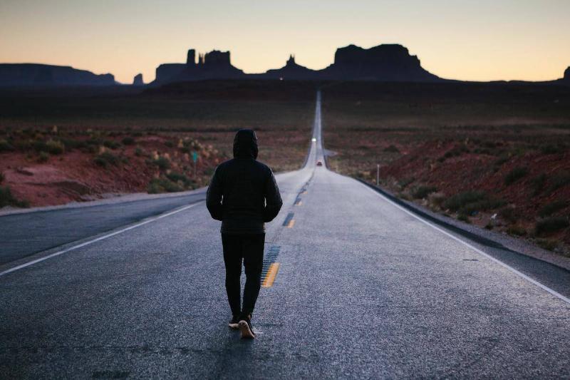man walks up an empty street in rural setting