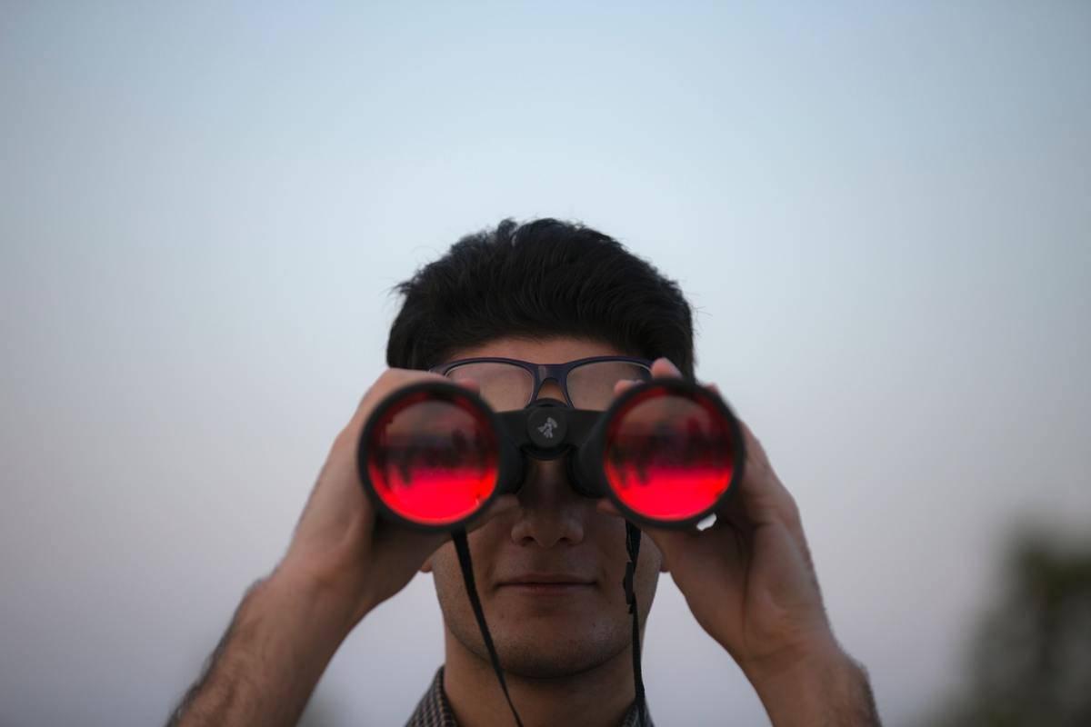 man looks through red glass binoculars