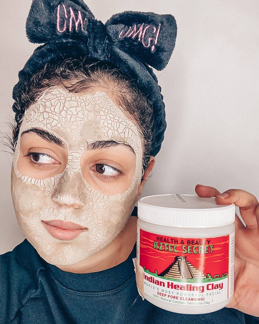 woman holding the clay mask with it in her hands
