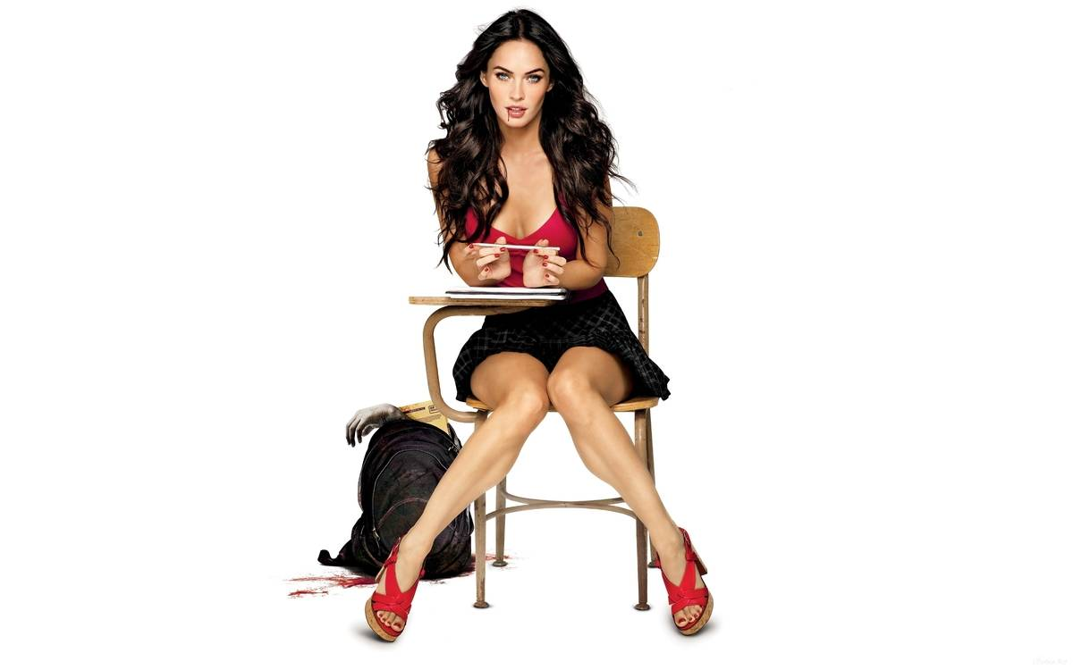 publicity still of megan fox in red shirt, black shirt, and red heels sitting at a desk