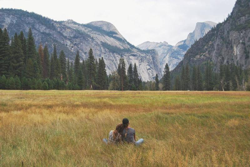 couple sitting in a field by the mountains