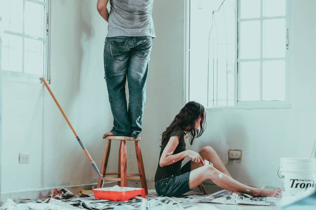 a couple painting a room together
