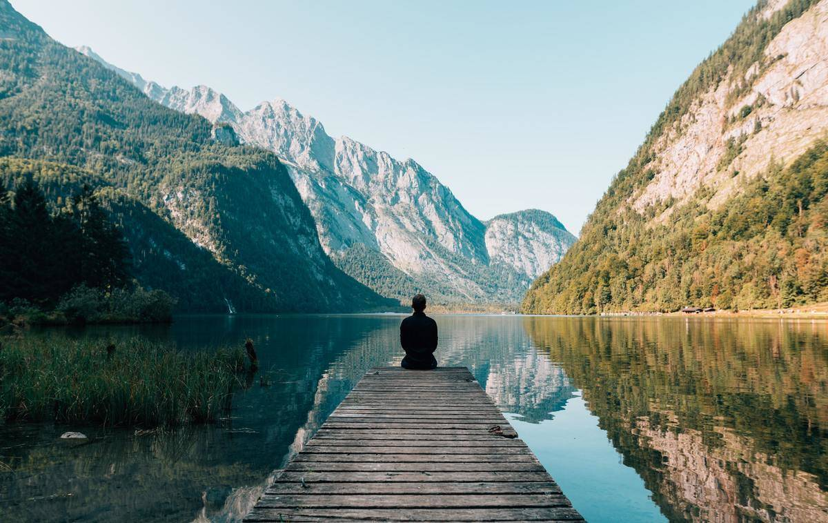 person sitting on dock in mountains