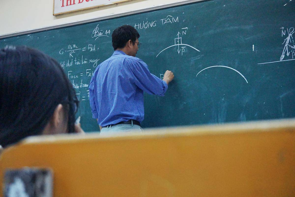 professor teaching at chalk board
