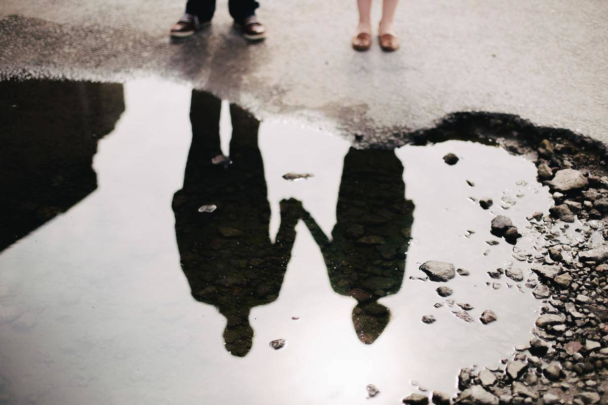 a picture of a couple's reflection in a puddle