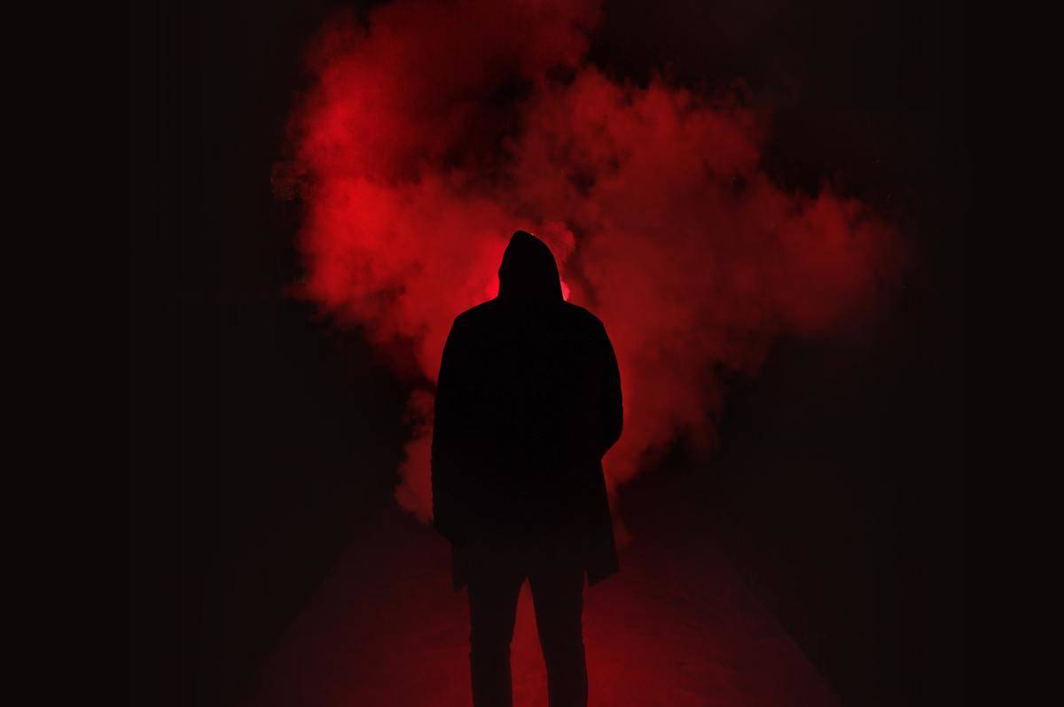 silhouette of man in front of red light