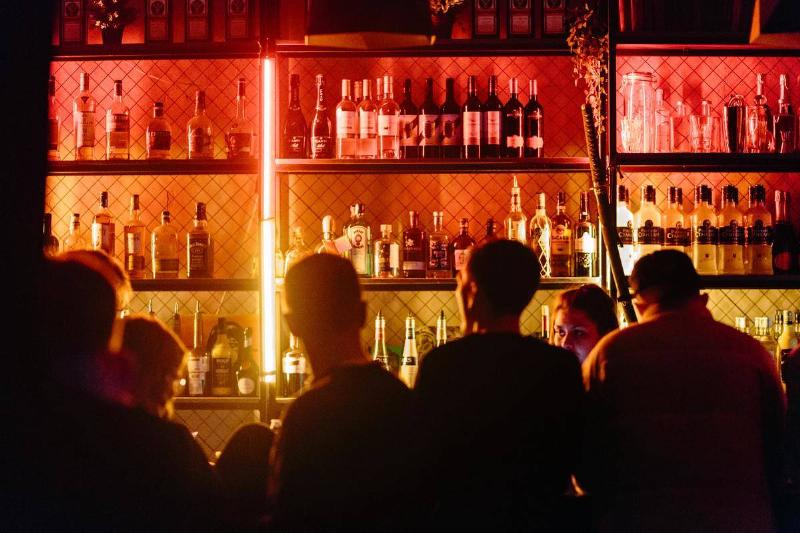 silhouettes of people standing at bar