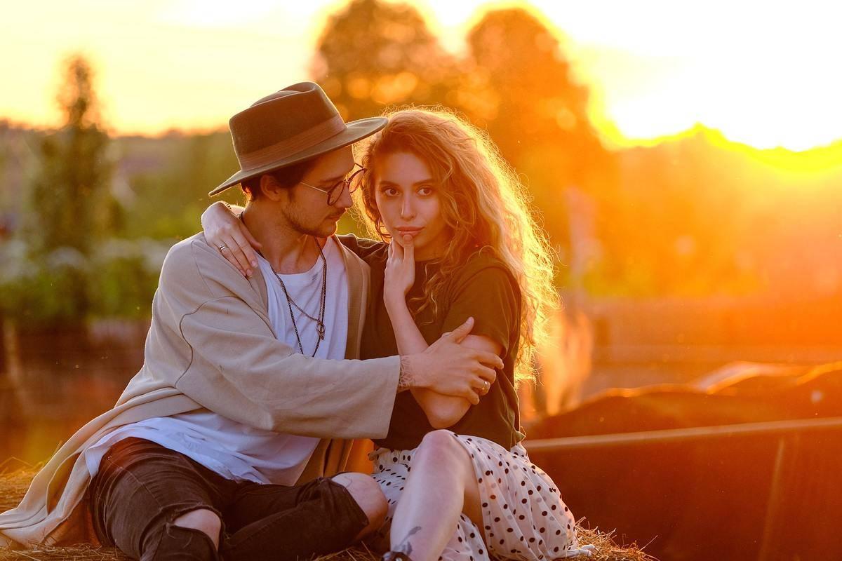 couple sitting outside at sunset, man staring at woman, woman staring at viewer