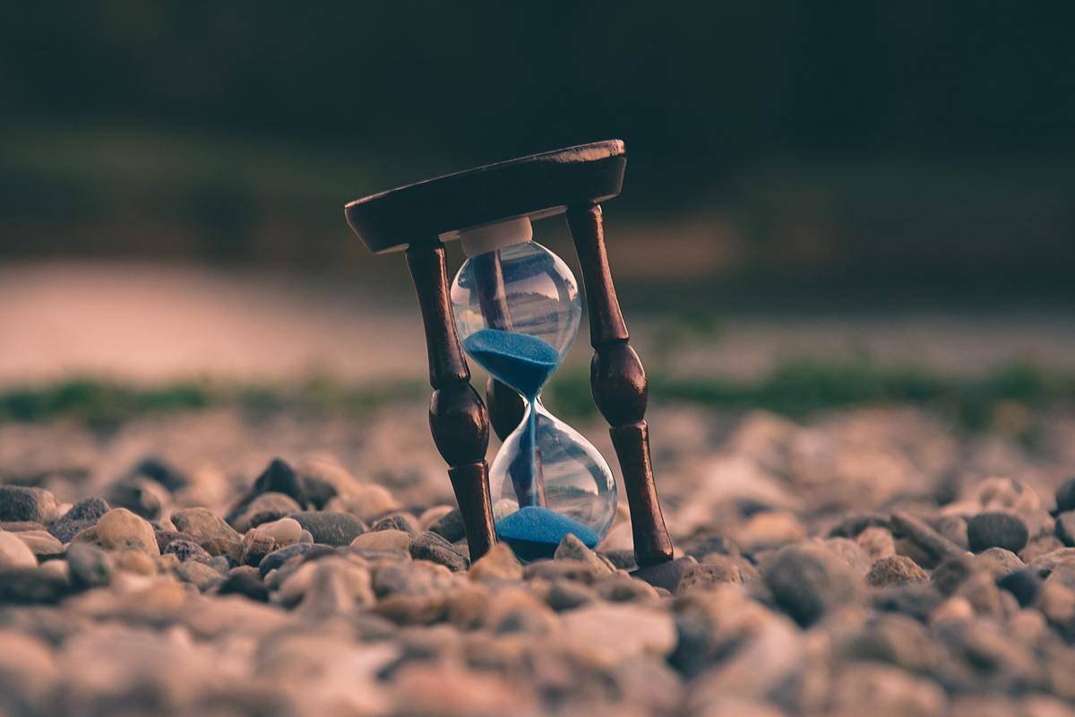 hourglass propped up among pebbles