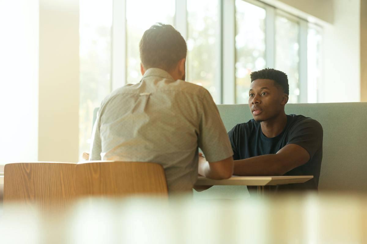 two men seated talking