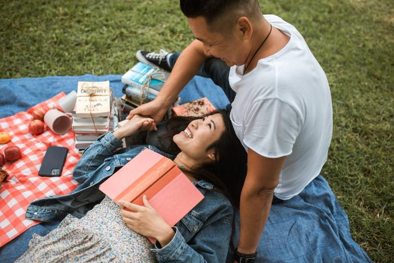 woman and man on picnic blanket in park