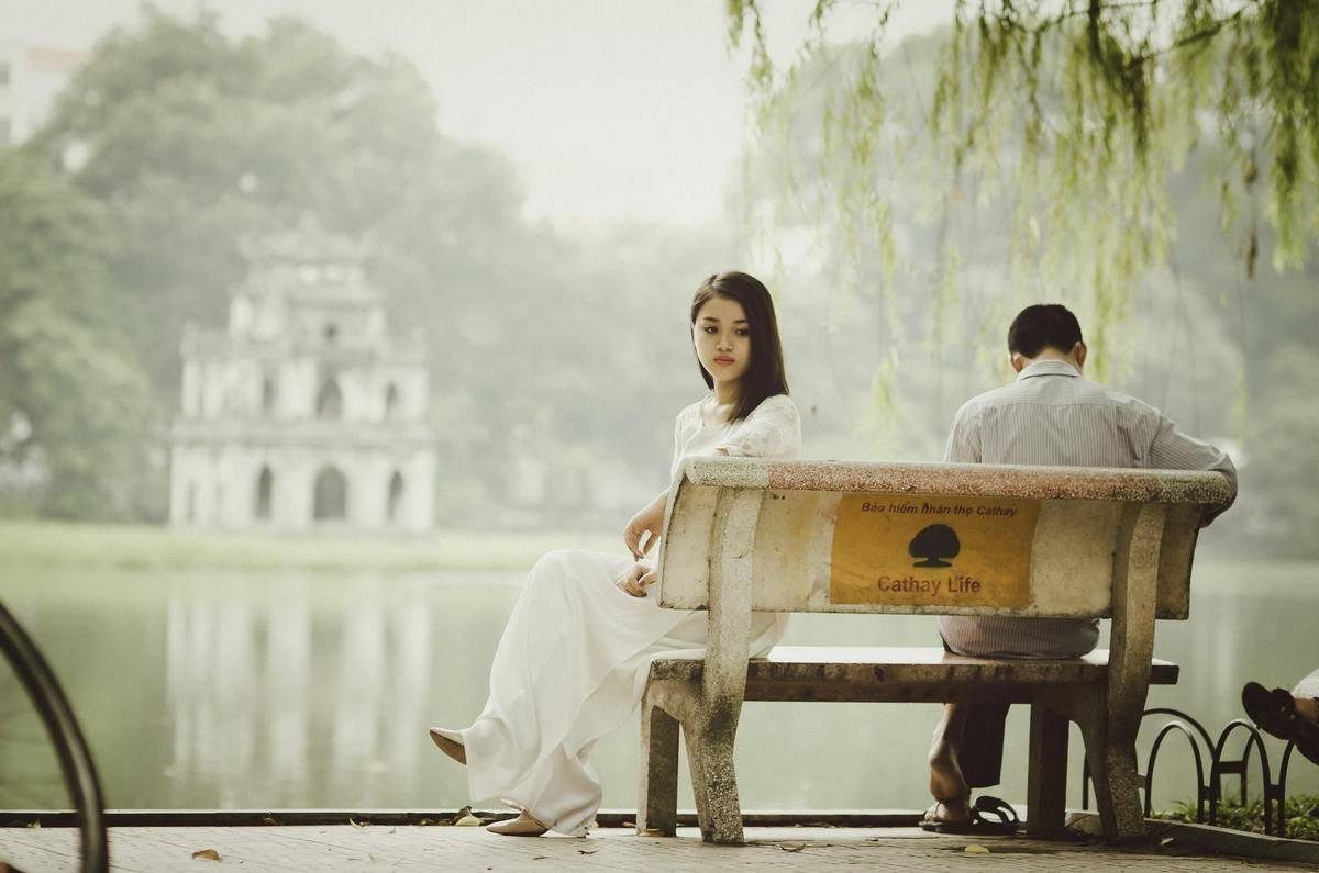 woman and man sitting apart on a park bench