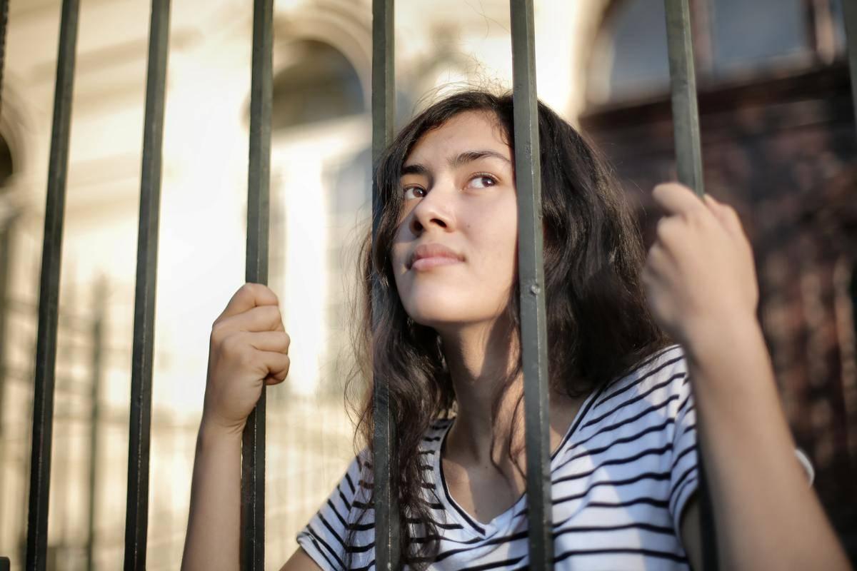 woman stuck behind bars