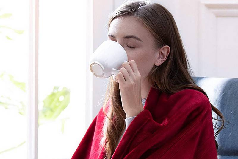 woman drinking coffee on desk chair wrapped in red blanket