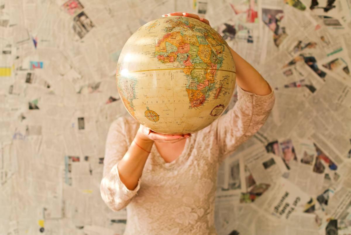 woman holding a rotating globe
