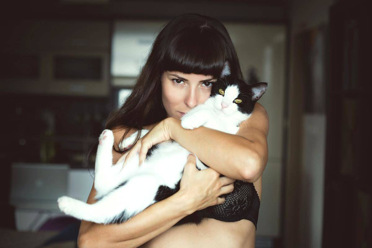 woman holds cat close to her