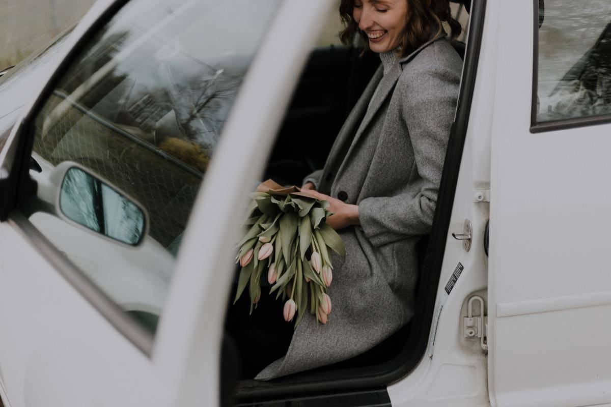 woman with flowers seated in car