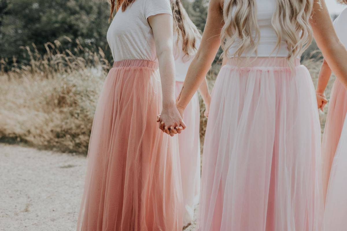 women holding hands wearing matching pink skirts