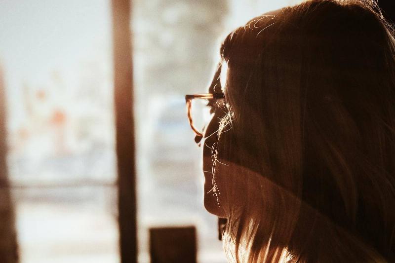 woman lookin at window in the sun