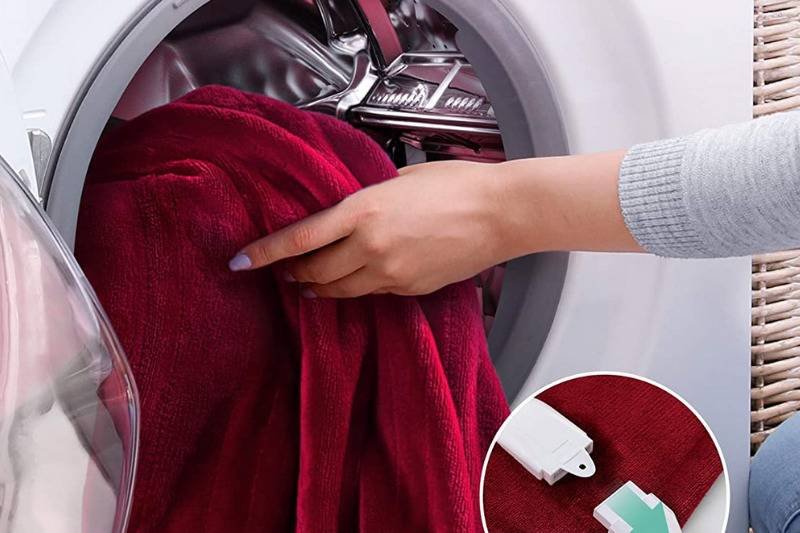 woman puts red blanket in washing machine