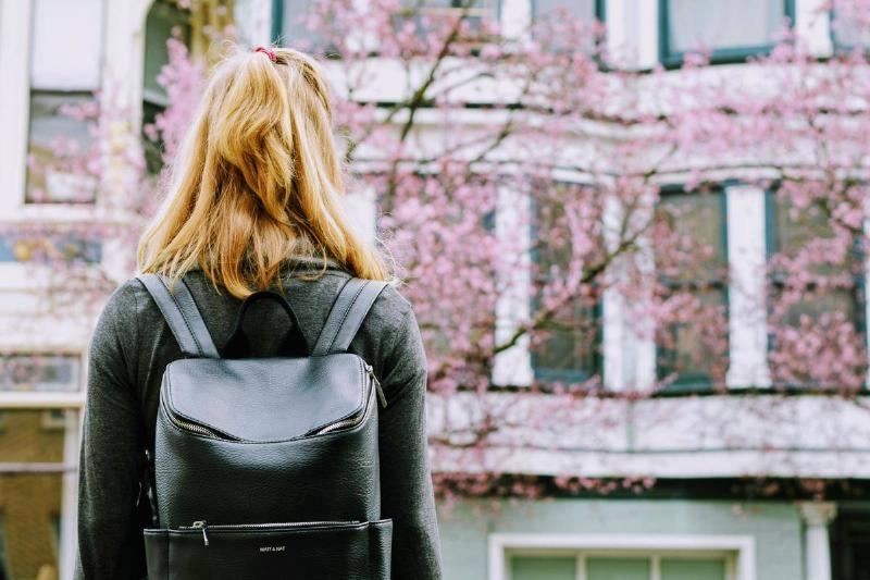 woman standing alone wearing backpack