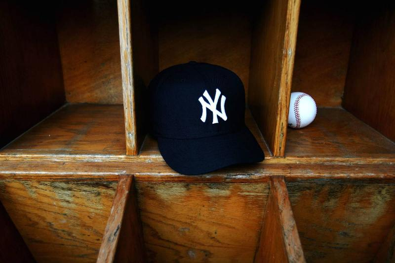 A New York Yankees cap and a baseball are seen at Legends Field