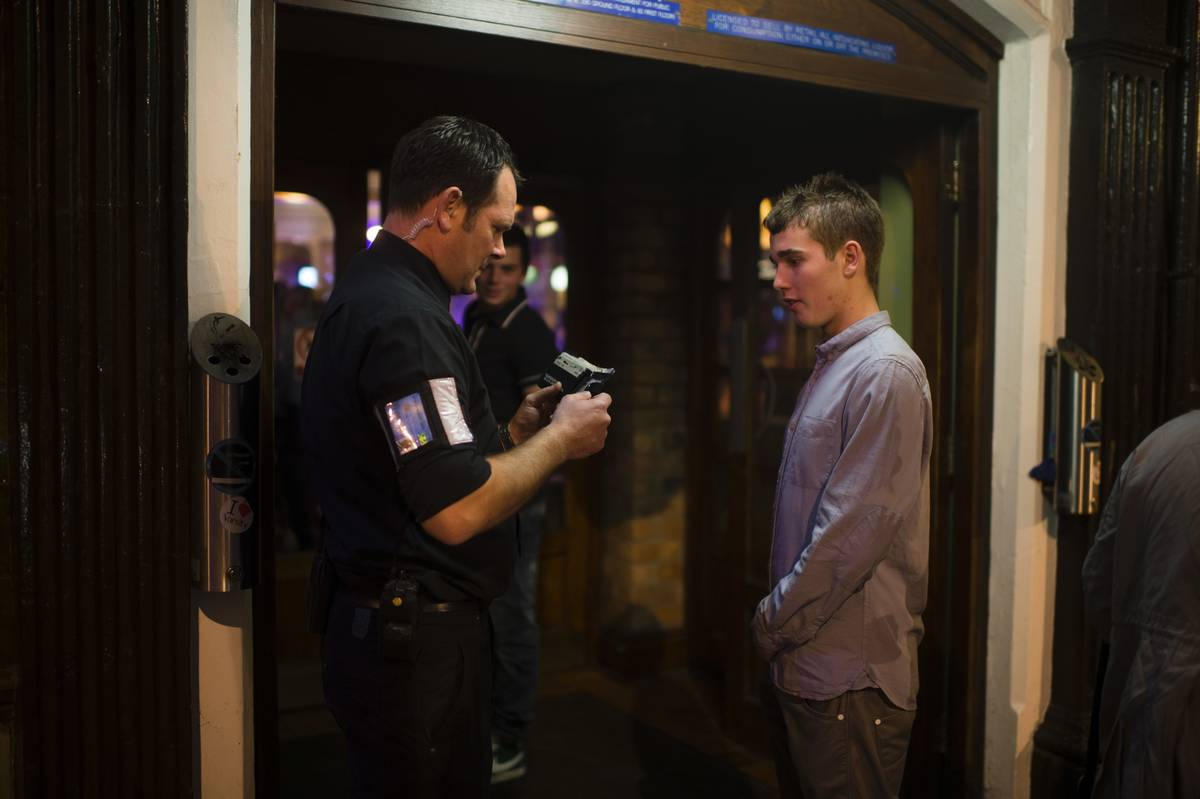A door security guard checking the age ID of a young man going into a pub