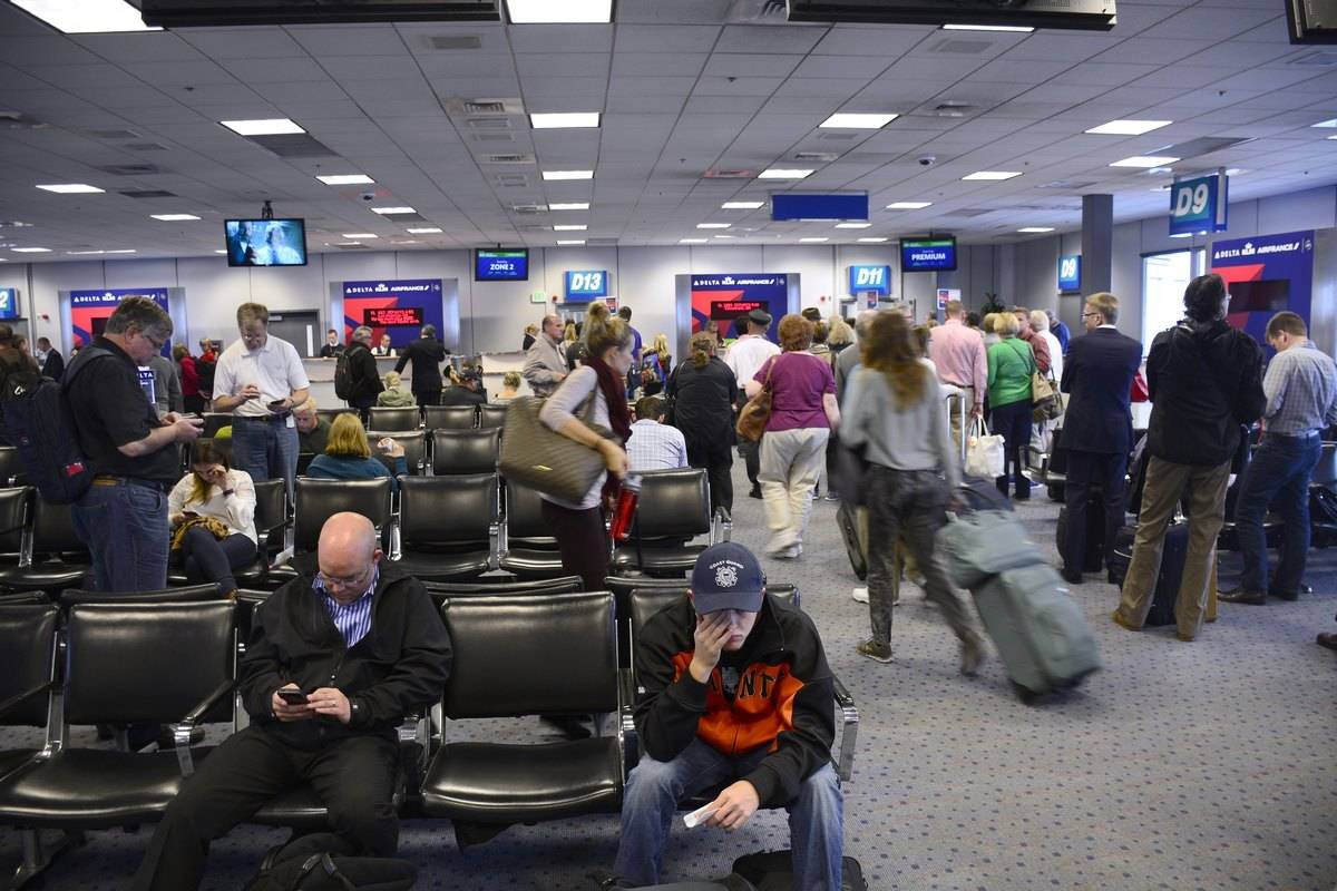 Airplane passengers wait for their flights to be called while others line up to board at Salt Lake City International Airport